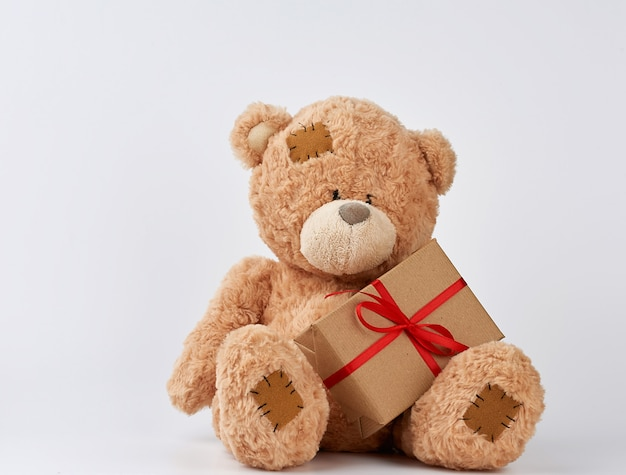 Cute big beige teddy bear holds a brown box with a red ribbon