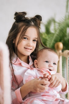 Симпатичная старшая сестра с новорожденным ребенком