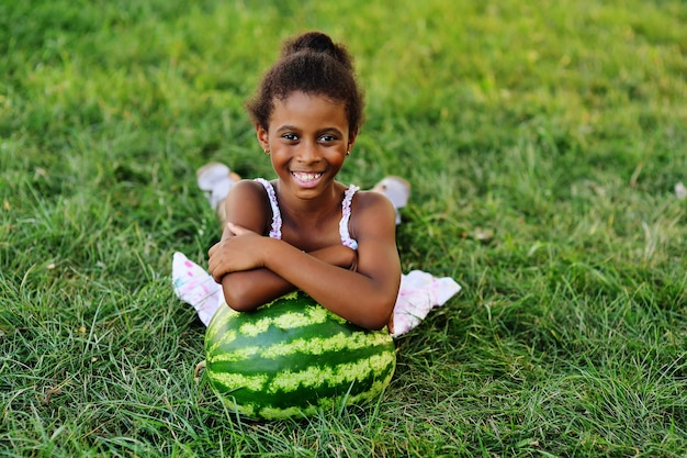 Cute black african american girl lying leaning on a big watermelon in the park on a sunny summer day