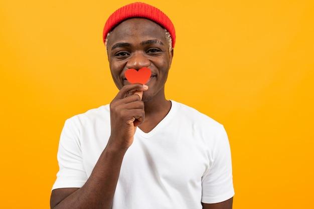 흰색 티셔츠에 귀여운 흑인 미국 사람은 노란색 배경에 발렌타인 데이 카드를 보유하고
