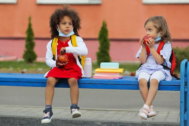 かわいい黒と白の女子学生がお弁当から学校の屋外で食べています。
