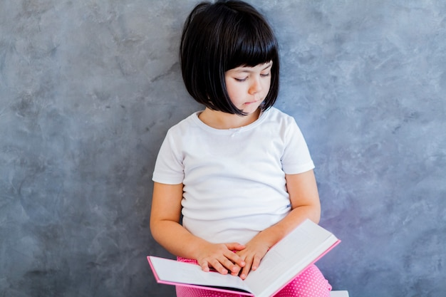 Cute black hair little girl reading book by the wall