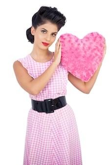 핑크 하트 모양의 베개를 들고 귀여운 검은 머리 모델