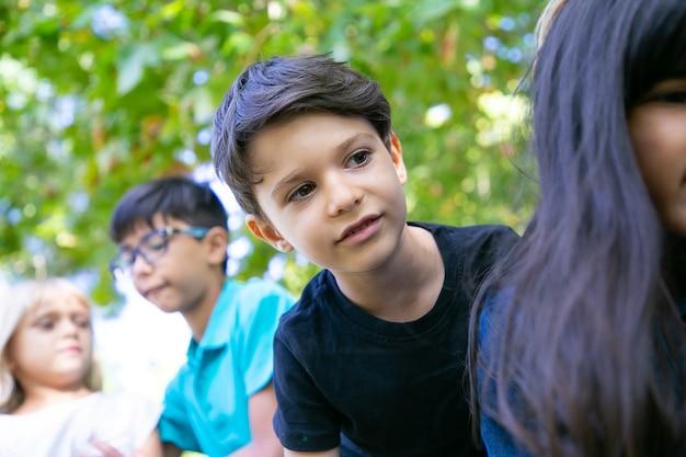 Ragazzo dai capelli neri sveglio che gode delle attività all'aperto, giocando con gli amici nel parco. gruppo di bambini che si divertono all'aperto. concetto di infanzia