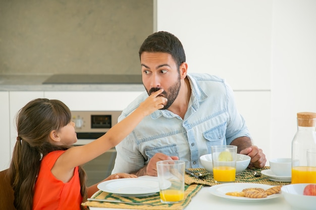 Cute black haired girl giving slice of food to her dad for tasting and biting