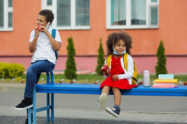 Cute black schoolboy and girl are eating outdoors the school.