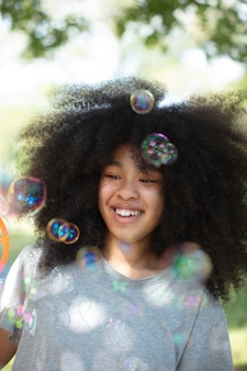 シャボン玉で遊ぶかわいい黒人の10代の少女