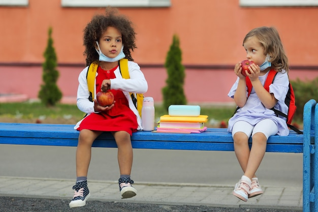 Cute black and white schoolgirls are eating outdoors the school from lunchbox.