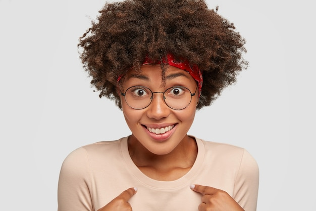 Cute black woman smiles happily, feels proud of her deeds, asks about something, being amazed she was picked, has curly hairstyle, models against white wall, overwhelmed with positive emotions
