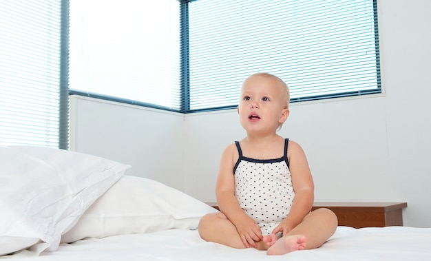 Cute blond baby sitting on bed alone