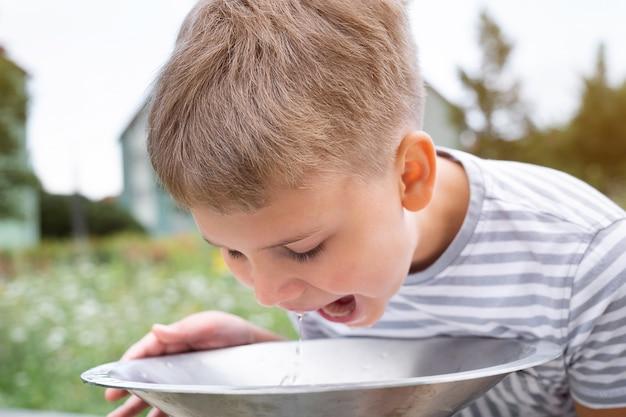 도시 공원에 있는 공공 음용 분수 수도꼭지에서 물을 마시는 귀여운 금발 소년