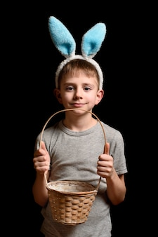 Cute blond boy in hare's ears holding a wicker basket on a black
