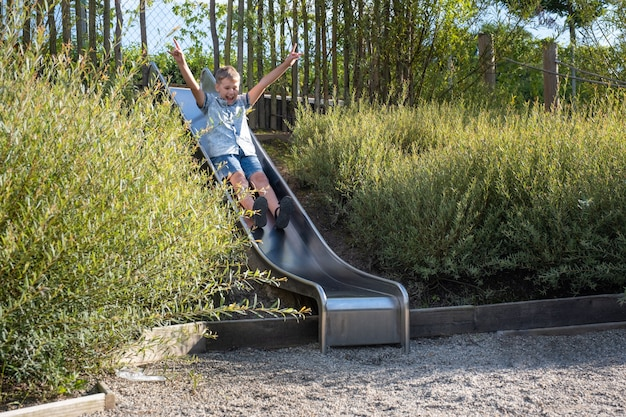 Cute blond boy swinging on a public playground swing. kid play outdoors on warm sunny summer day.