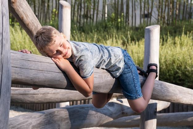 귀여운 금발 소년 소년은 공공 공원의 놀이터에 있는 나무 기둥에 누워 있습니다.