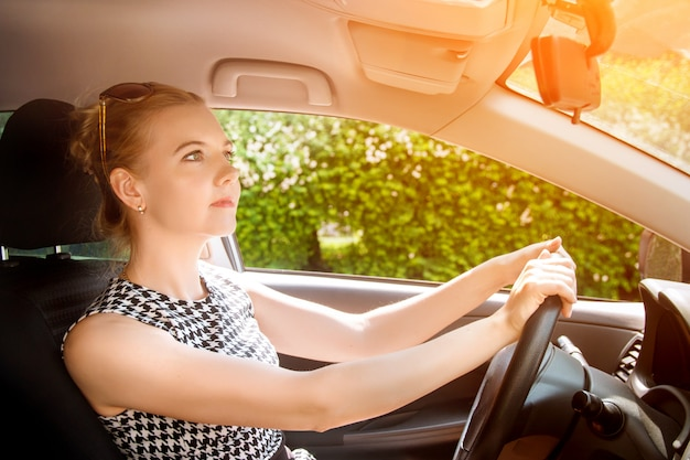 Cute blond business woman happy driving car.
