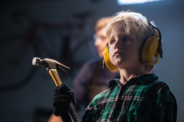 목수의 워크숍, 클로 우즈 업 초상화에에서 손에 망치로 귀여운 금발 아이 소년.