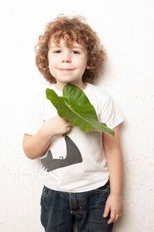 Милый белокурый кудрявый мальчик смотрит в камеру с растением