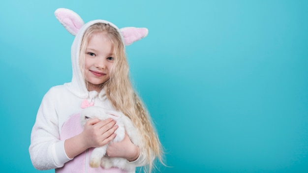 Cute blond girl in bunny ears with rabbit