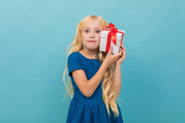 Cute blond girl in a dress with a gift in her hands on light blue with copy space