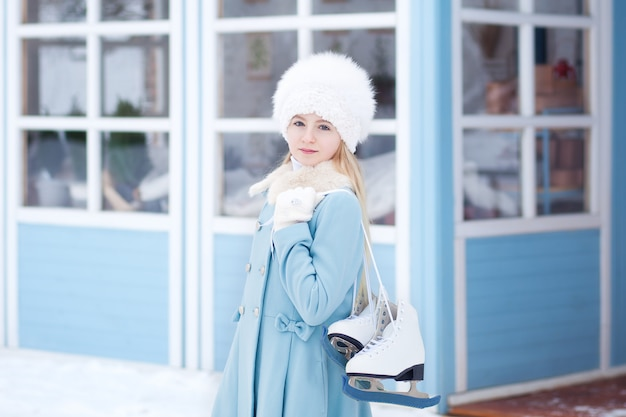 A cute blond girl is going to skate outdoors. a girl in a blue coat and fur hat with skates at the winter house. weekend activities in cold weather. christmas, winter holidays concept. winter sport.