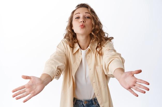 Carina ragazza bionda che bacia, allunga le mani per abbracciare o coccolare qualcuno di caro, in piedi romantico e sciocco contro il muro bianco