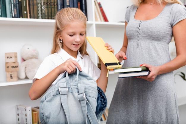 Милая, белокурая девушка кладет книги в рюкзак, мама помогает ей ходить в школу