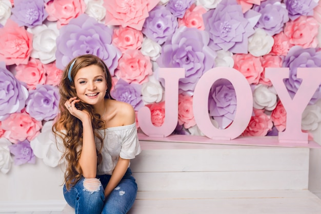 Cute blond girl sitting on a bench in a studio smiling widely. she has pink background covered in flowers with word joy