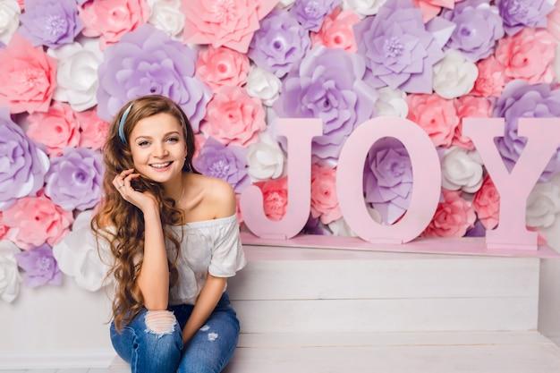 広く笑みを浮かべてスタジオのベンチに座っているかわいいブロンドの女の子。彼女はピンクの背景に喜びの言葉で花で覆われています