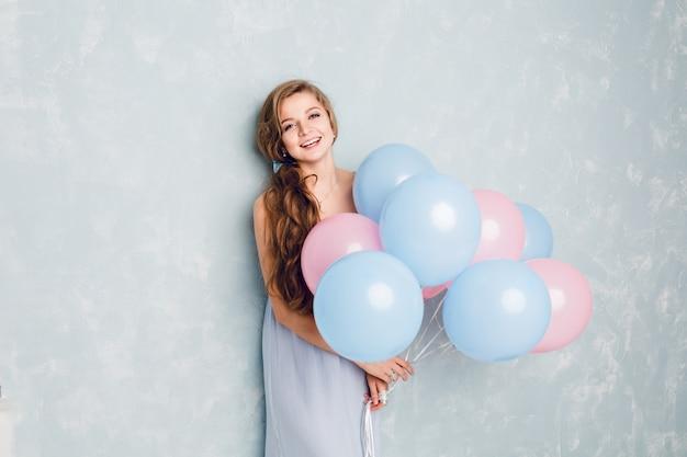 スタジオに立っている笑顔と青とピンクの風船を保持しているかわいいブロンドの女の子。
