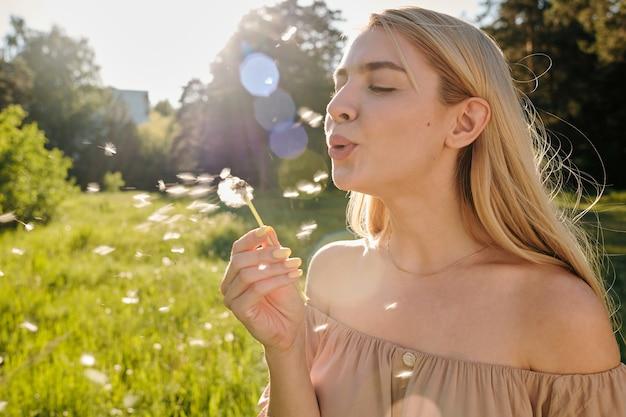 Милая блондинка с длинными волосами дует одуванчик, наслаждаясь солнечным летним днем с зеленой травой и деревьями
