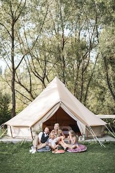 Симпатичные белокурые девочки с родителями сидят возле большой палатки вигвама и едят фрукты, арбуз.