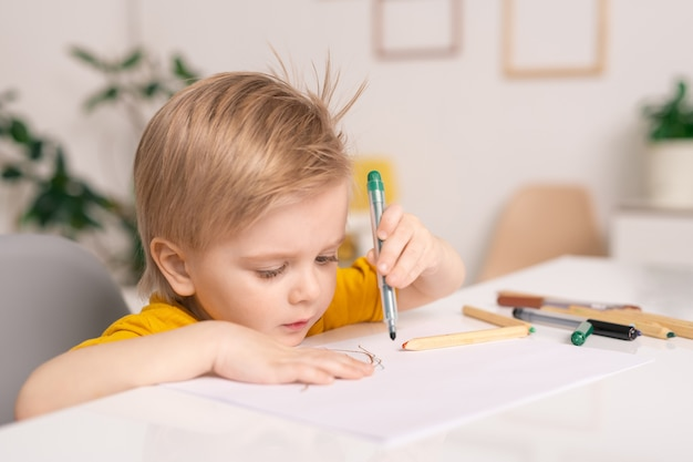 Cute blond little boy with green crayon or highlighter over paper drawing picture by desk while staying at home on quarantine