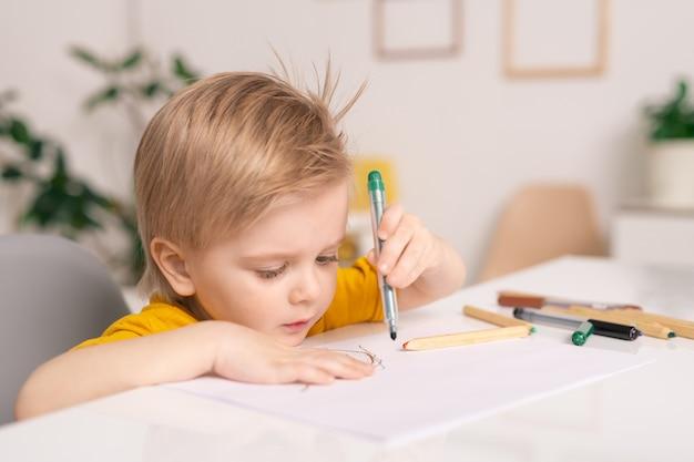 Симпатичный белокурый маленький мальчик с зеленым мелком или маркером над бумагой, рисующий картину за столом, оставаясь дома на карантине