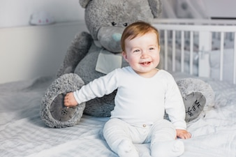 Cute blonde baby in white bed with teddy bear