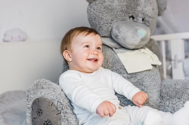 테 디 베어와 함께 흰색 침대에 귀여운 금발 아기