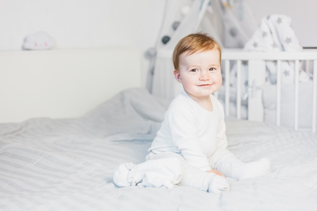 Cute blonde baby in white bed