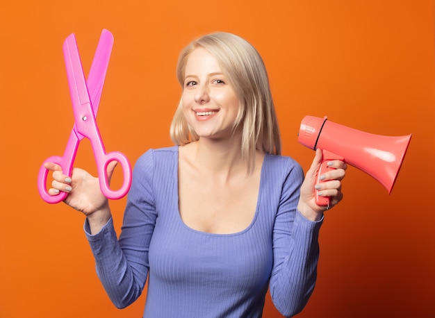 Cute blonde in blue blouse with big scissors and megaphone on an exuberant orange color background
