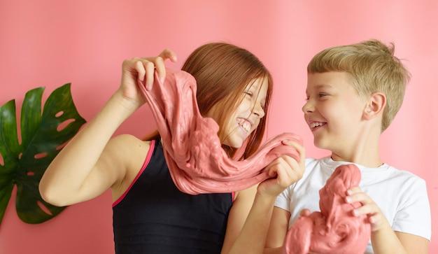 かわいい金髪の少年とピンクの背景に手作りスライムで遊んで赤い髪の少女
