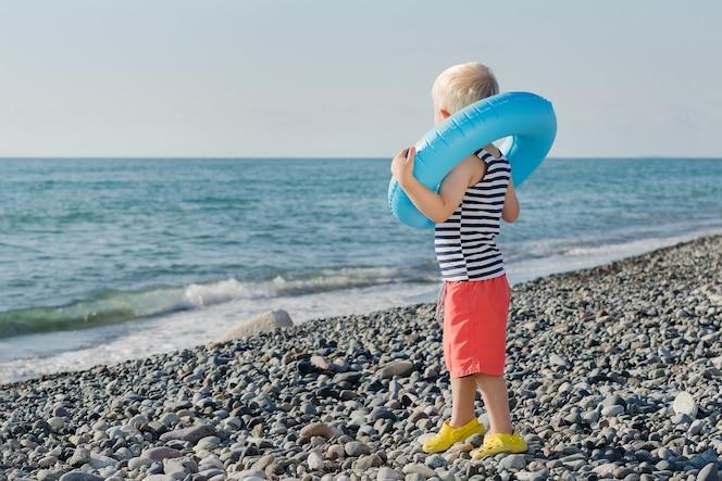 Симпатичный белокурый мальчик одет в надувное кольцо и смотрит на море
