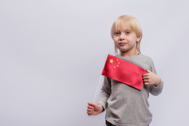 Cute blonde boy holds a flag of china. education in china. learning chinese