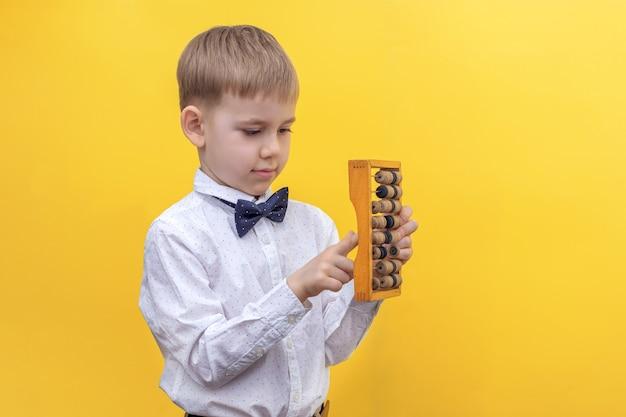 木製のそろばんを保持しているシャツを着たかわいい金髪の少年知識の日の概念