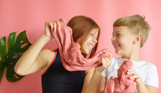 Cute blonde boy and red hair girl playing with handmade slime on pink background