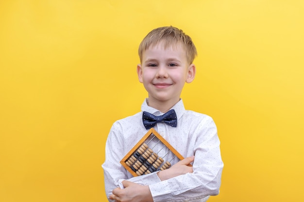 Cute blonde boy in a shirt holding a wooden abacus
