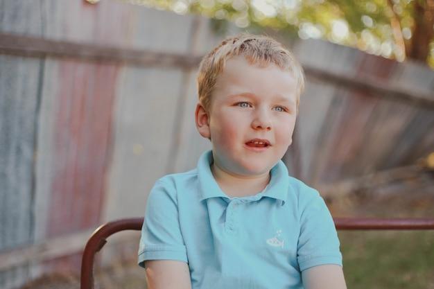 青いポロシャツを着て、遊び場でポーズをとってかわいい金髪の少年