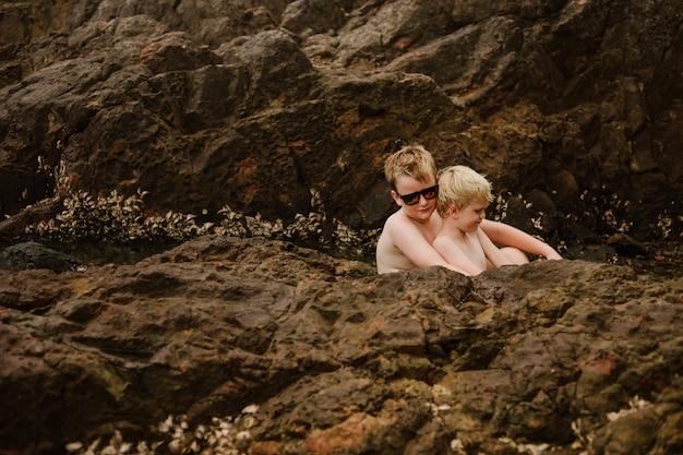 ビーチでポーズをとってかわいい金髪の兄弟
