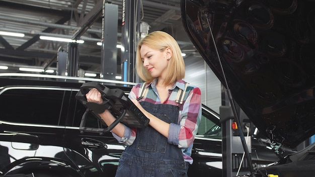 Cute blonde car mechanic engaged in car diagnostics, small business