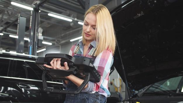 Cute blonde car mechanic working in a car service
