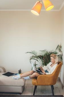 Милая белокурая кавказская женщина сидит за ноутбуком после онлайн-уроков и улыбается