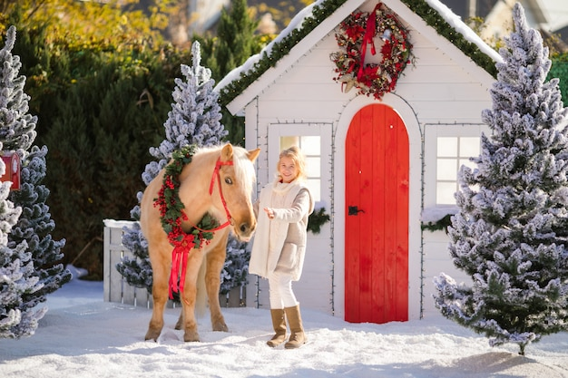 Cute blonde girl and adorable pony with wreath near the small house and snow-covered trees.