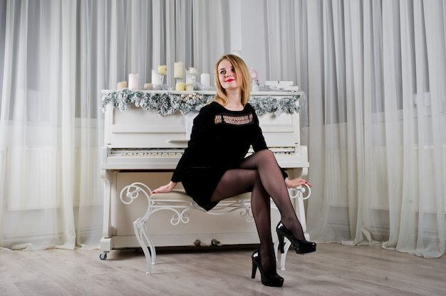 Cute blonde girl on black dress against new year piano with christmas candles.